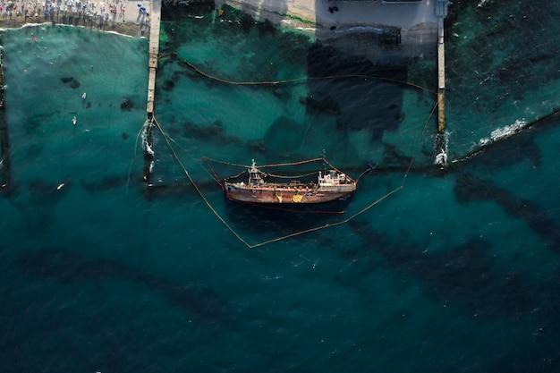 Вид сверху на старый танкер, севший на мель и перевернувшийся