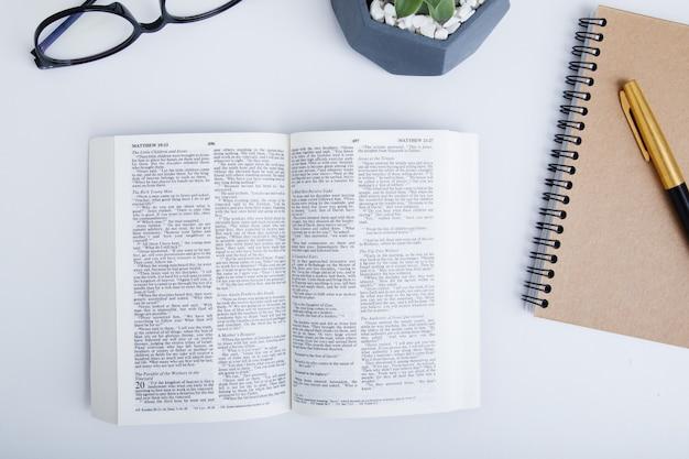 펜과 안경 흰색 테이블에 오픈 성경의 상위 뷰