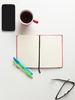 Вид сверху открытой красной тетради, сине-зеленая ручка, красная чашка кофе