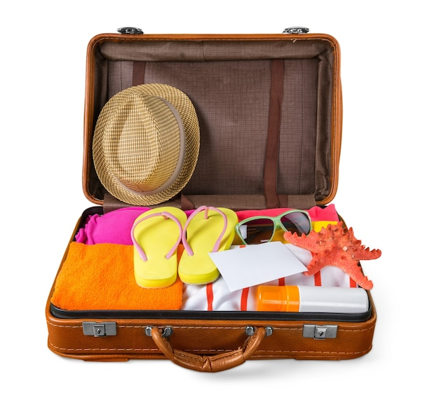 青い背景に夏のものでいっぱいのオープンスーツケースの上面図