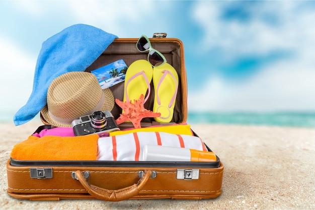 Вид сверху на открытый чемодан с полным летним хламом на синем фоне