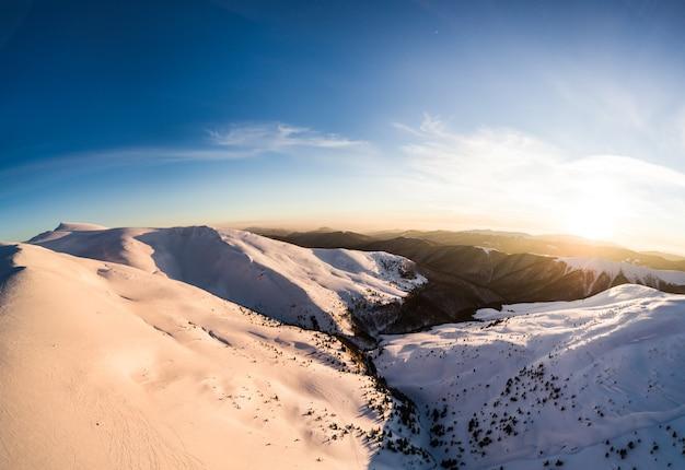 Вид сверху незабываемого горнолыжного спуска, покрытого снегом, расположенного в горах в северной стране в солнечный зимний холодный вечер. понятие красоты северной природы. copyspace
