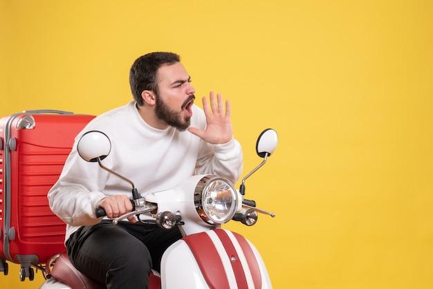 孤立した黄色の背景に誰かを呼び出すスーツケースを持ってオートバイに座っている怒っている若い男のトップ ビュー