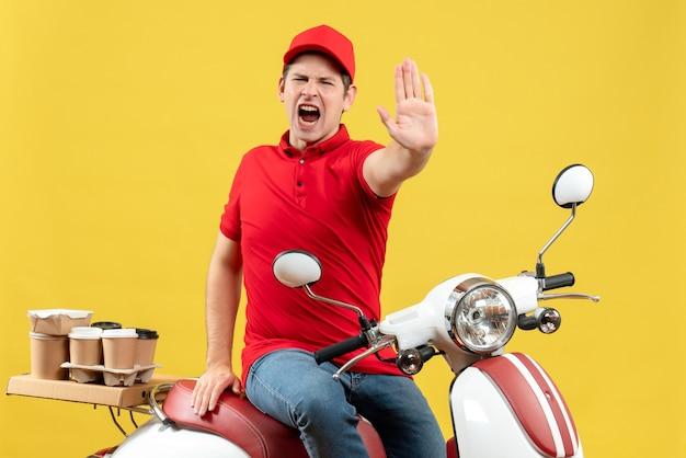赤いブラウスと帽子をかぶって、黄色の背景に停止ジェスチャーを示す注文を配信している怒っている若い男の上面図