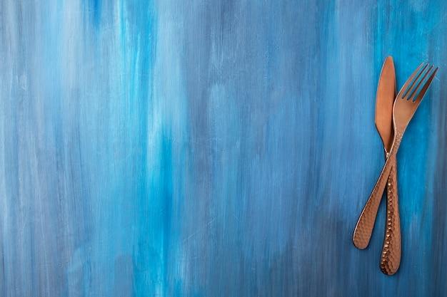 青い背景の上のantigueナイフとフォークの上面図。コピースペース付き