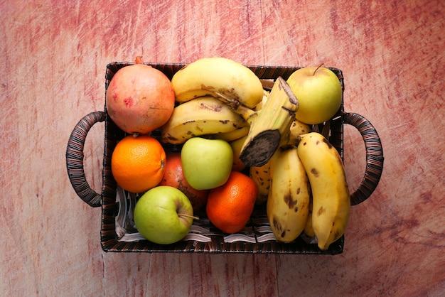Вид сверху яблока, банана и апельсина в миске на столе