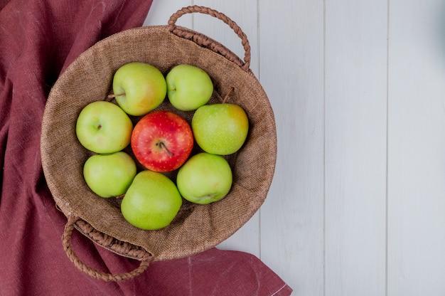 Взгляд сверху яблок в корзине на ткани bordo и деревянной предпосылке с космосом экземпляра