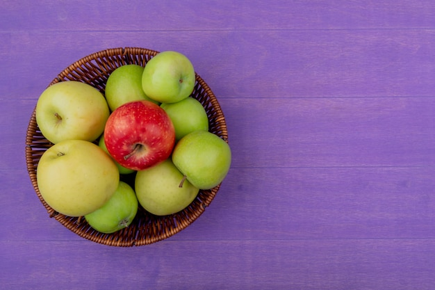 Вид сверху яблок в корзине на фиолетовом фоне с копией пространства