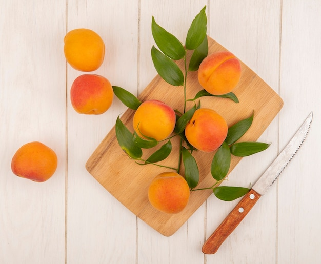 Вид сверху абрикосов и листьев на разделочной доске с ножом на деревянном фоне