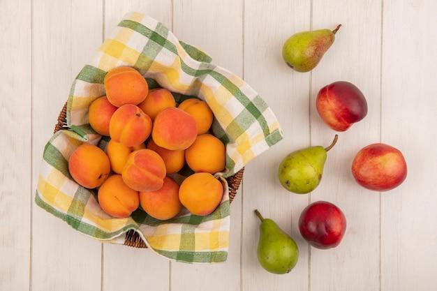 Вид сверху абрикосов в корзине с грушами на деревянных фоне