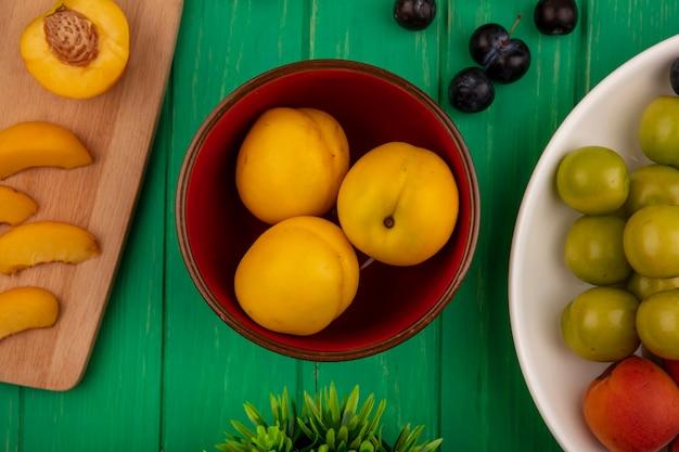 그릇에 살구의 상위 뷰와 녹색 배경에 그릇에 자두와 슬로 열매를 절단 보드에 잘라 슬라이스 것들