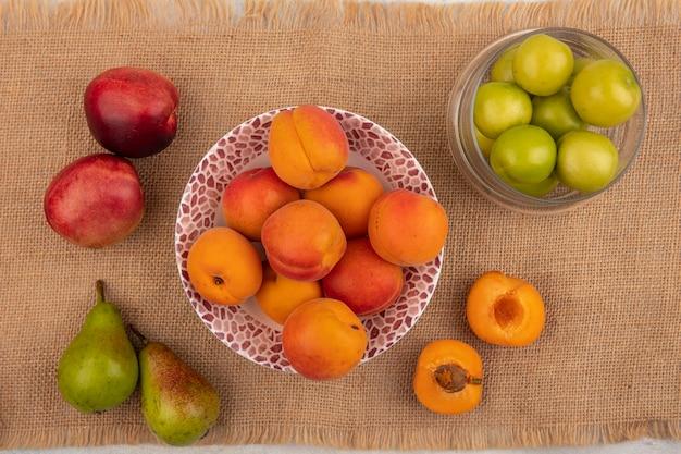 Вид сверху на абрикосы в миске и половину разрезанных груш персиков и миску слив на фоне мешковины