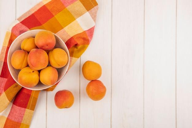 Вид сверху абрикосов в миске на клетчатой ткани и на деревянном фоне с копией пространства