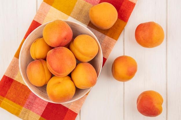 Вид сверху абрикосов в миске на клетчатой ткани и на деревянном фоне
