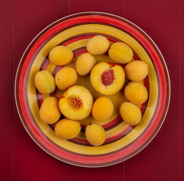 Вид сверху абрикосов с персиком на тарелке на красной поверхности