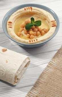白いテーブルにアラビア語のフムスと包まれたパンとヘシアンの袋のトップビュー
