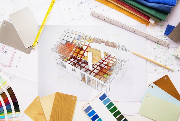 Вид сверху на проект рабочего стола архитектора в окружении инструментов и материалов