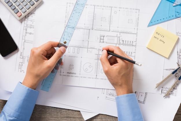 Вид сверху архитектора, рисующего новый проект на светокопии. крупным планом руки человека работают и зарисовки строительного проекта на офисном столе. проект нового дома.
