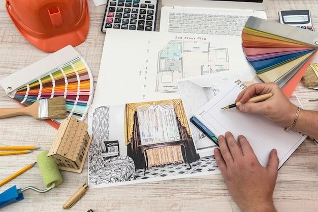 창의적인 테이블에 샘플 자료, 안전모, 노트북으로 현대 집을 그리는 건축가의 상위 뷰
