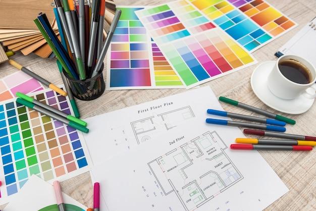 創造的な机の上の材料のサンプルと建築設計図の上面図。