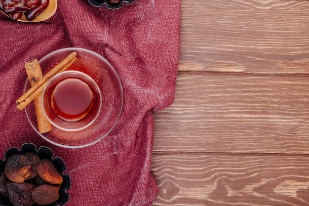 コピースペース付きの木製の背景にシナモンスティックとミニのタルト缶でアプリコットを乾燥させたお茶のアルムドゥガラスのトップビュー