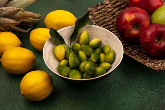 緑の壁に隔離されたレモンと籐のトレイに新鮮な赤いリンゴとボウルの芳香族キンカンの上面図