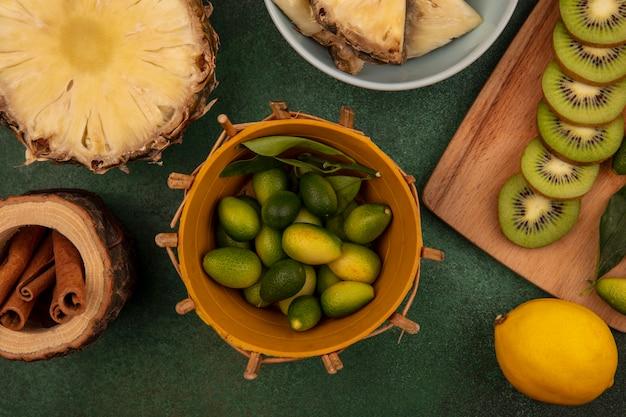緑の背景に分離されたレモンとシナモンスティックとボウルにパイナップルとパイナップルと木製のキッチンボードにキウイスライスとバケツの芳香族キンカンの上面図