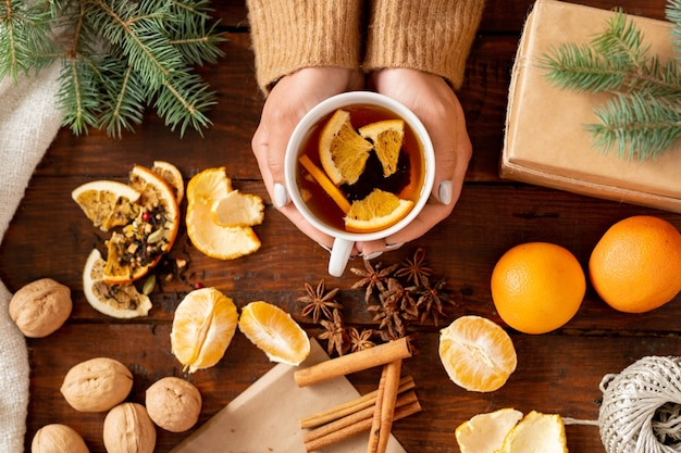 Вид сверху ароматного чая с дольками апельсина в руках женщины в окружении свежих фруктов, специй и грецких орехов на деревянном столе