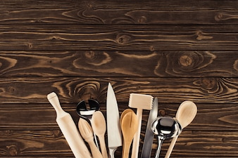 Top view of arranged kitchen utensils on wooden table