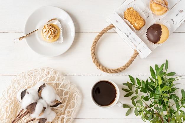 プレートとトレイに各種ミニケーキ、白い背景の上のコーヒーと緑の葉の配置の上面図。