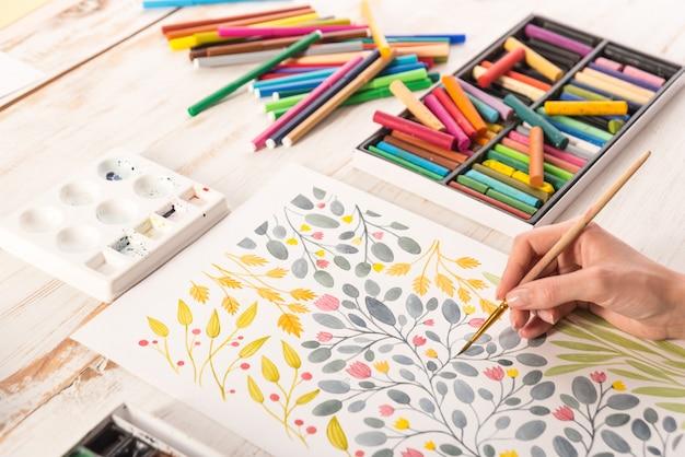 職場で花のデザインを描くアーティストのトップビュー