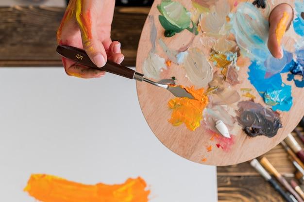 Вид сверху живописи художника с использованием инструмента и палитры