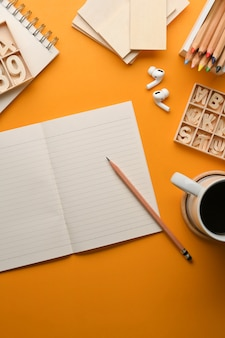 黄色のテーブルに文房具、クラフト要素、コーヒーカップとアーティストワークスペースの上面図