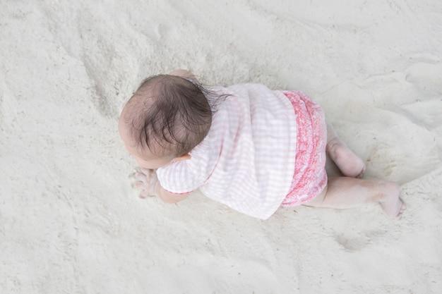 砂の上を這うアジアの赤ちゃんのトップビュー