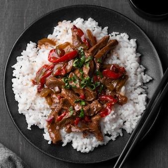 Вид сверху азиатского блюда с рисом и палочками для еды
