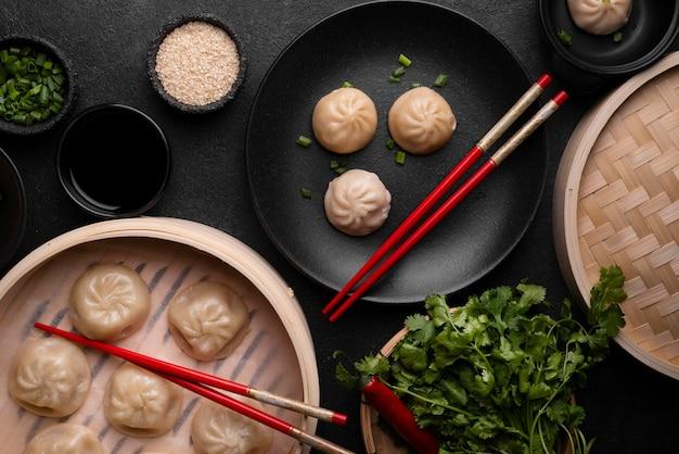 Вид сверху азиатских пельменей с палочками для еды и зеленью