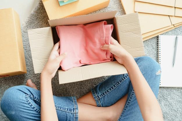 アジアの女の子の上面図は、顧客の注文に従って小包ボックスの中にピンクの服を準備しています。