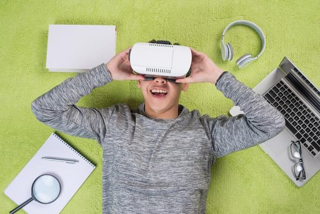 Вид сверху азиатского человека в очках виртуальной реальности. человек лежал на полу.
