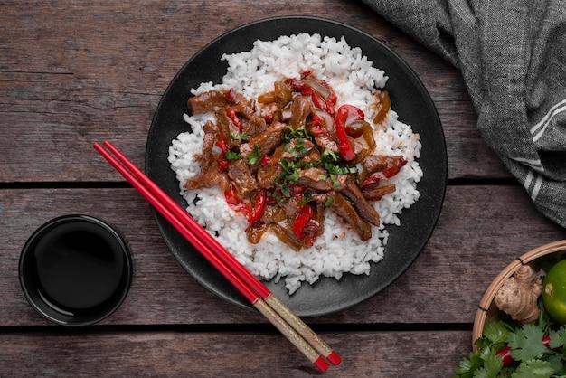 Вид сверху азиатского рисового блюда с мясом и палочками для еды