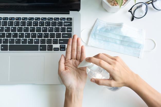 アジアの女性の手の上面図は、オフィスのワークデスク上で医療用フェイスマスクで手を消毒するために消毒ジェルを適用します。パンデミックおよび社会的排除の期間中の予防措置。
