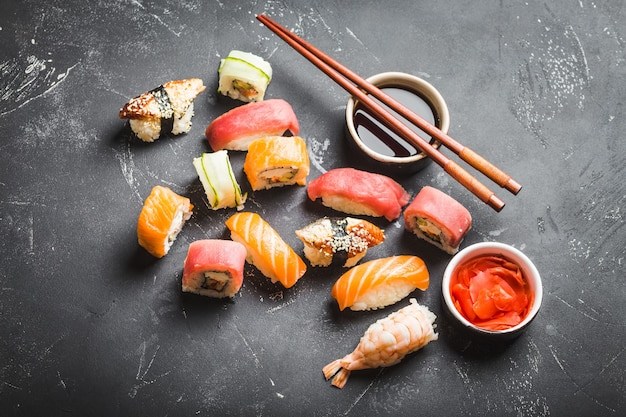 Вид сверху ассорти смешанных японских суши с роллами, нигири, соевым соусом, имбирем, палочками на черном фоне бетона. азиатский ужин или обед