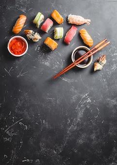 Вид сверху ассорти смешанных японских суши с роллами, нигири, соевым соусом, имбирем, палочками для еды на черном бетонном фоне со свободным пространством для текста. азиатский ужин или обед