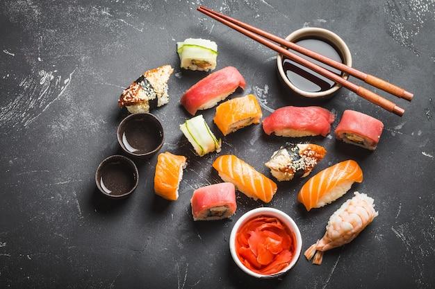 Вид сверху ассорти смешанных японских суши с роллами, нигири, соевым соусом, имбирем, палочками для еды, двумя чашками традиционного саке на черном фоне бетона. азиатский ужин или обед