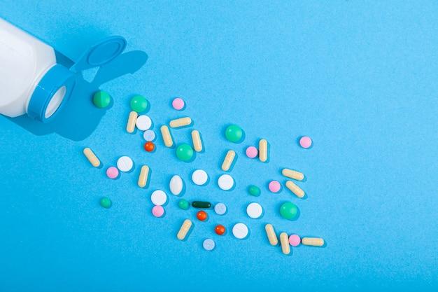 青い背景、食品栄養補助食品、医薬品ビタミン、水平、コピースペース、フラットレイにピルボトルのカラフルな錠剤やカプセルから散らばっている各種の上面図