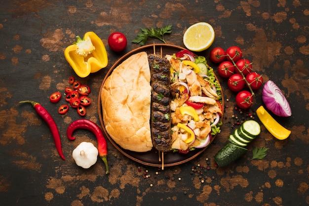 Вид сверху на ассортимент вкусных шашлыков с овощами