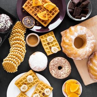 Вид сверху ассорти из пончиков с вафлями и шоколадом
