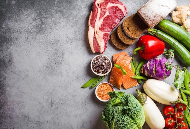 健康的なバランスの取れた食品の品揃えの上面図:肉、魚、野菜、パン、シリアル、豆、石の背景、テキスト用のスペース。健康的な食事を調理するための原材料、ダイエットに適した、きれいな食事