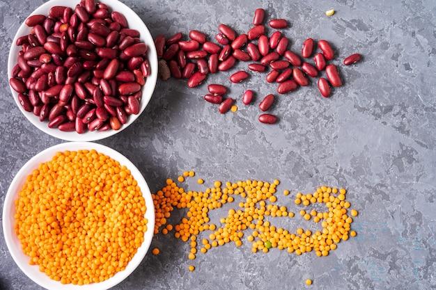 灰色の背景上のレンズ豆と豆の品揃えの平面図です。