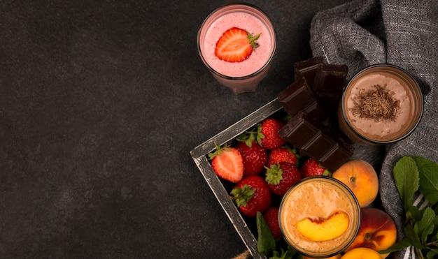 Вид сверху ассортимента стаканов для молочного коктейля на подносе с фруктами и шоколадом