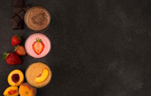 Вид сверху ассортимента молочных коктейлей с фруктами и шоколадом с копией пространства